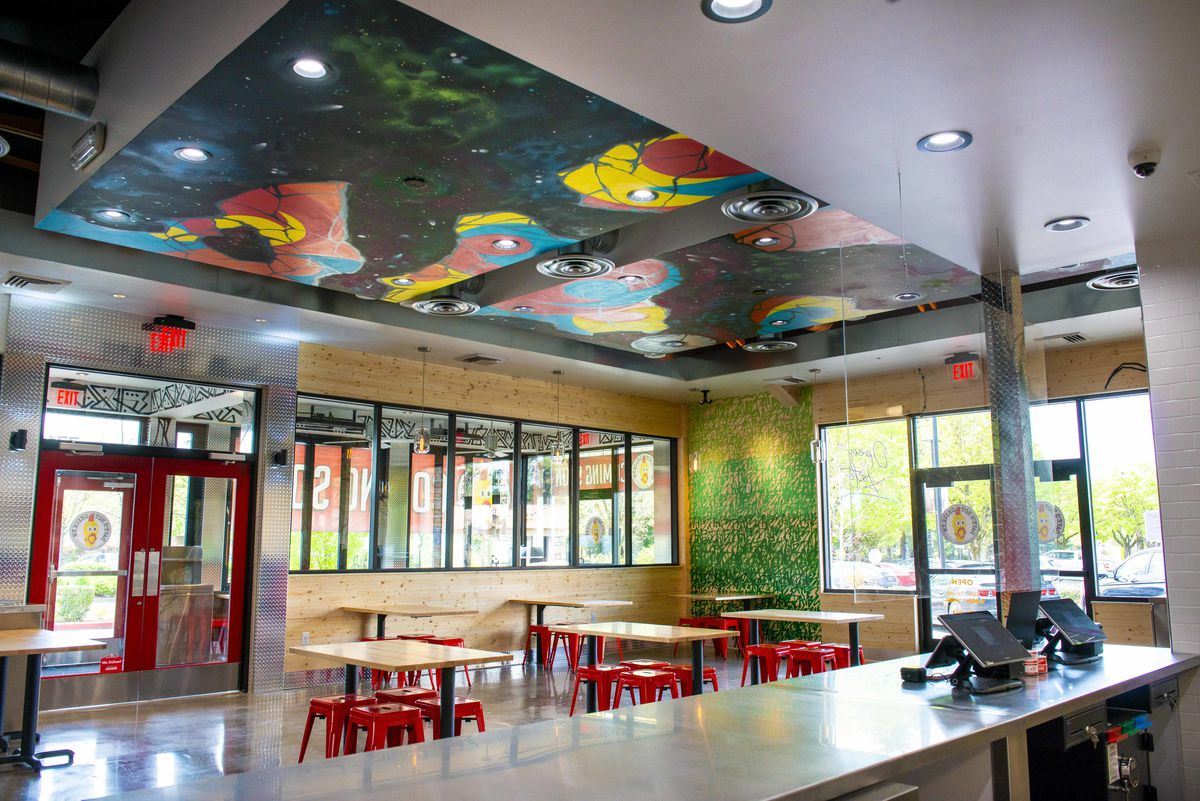 The ceiling of the new Dave's Hot Chicken location is meant to feel pseudo-galactic, with colors and star-like clusters of art. Along the sides of the walls are green and yellow patterns meant to mimic the natural spaces within Oregon.