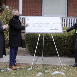 Joseph Grenny, chairman of the board of The Other Side Academy, right, looks at an oversize $100,000 check from businessmen David Ibarra, center, and K.O. Murdock, left, during a ceremony in front of academy in Salt Lake City on Thursday, Dec. 17, 2020. The academy is a 2 1/2-year residential program where those who have been involved in the criminal justice system can learn social, vocational and life skills. The funds will be used to expand the program and remodel a former senior living center that is next door to The Other Side Academy.