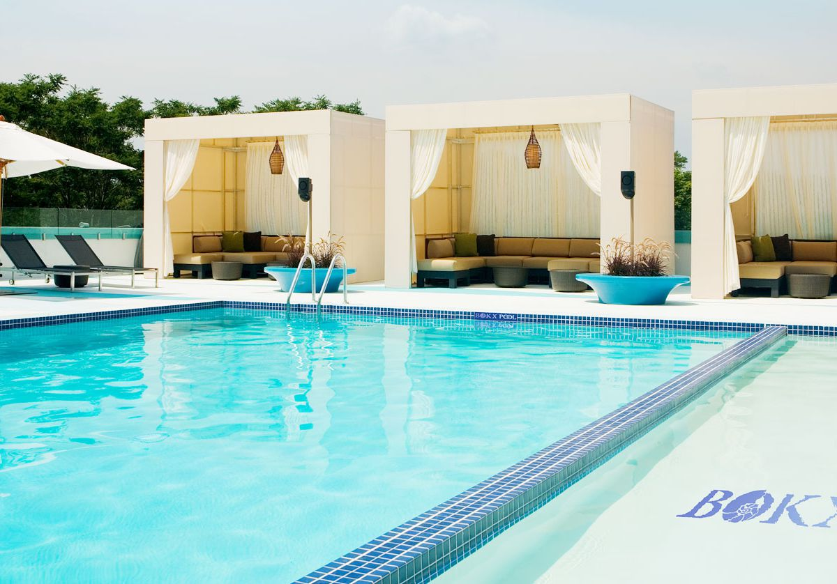 In the foreground is a swimming pool. There are lounge chairs and cabanas along the edge of the swimming pool.