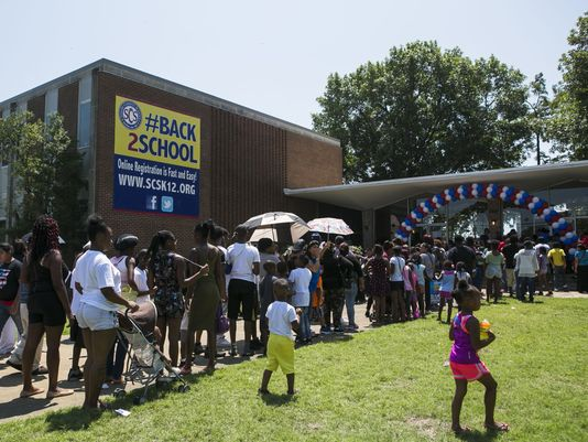 Parents wait outside Shelby County Schools central office to register children for school.