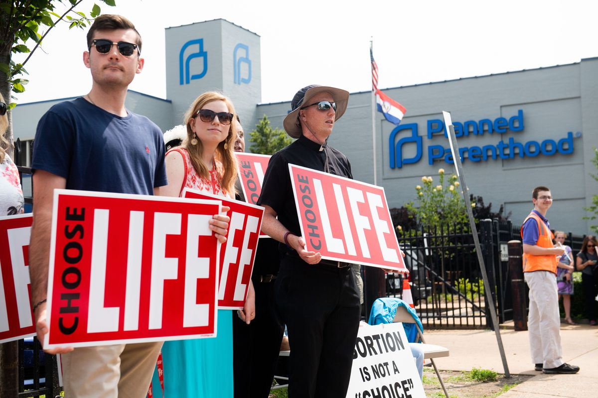"""Three anti-abortion protesters, holding signs reading """"Choose life,"""" stand outside a Planned Parenthood clinic."""