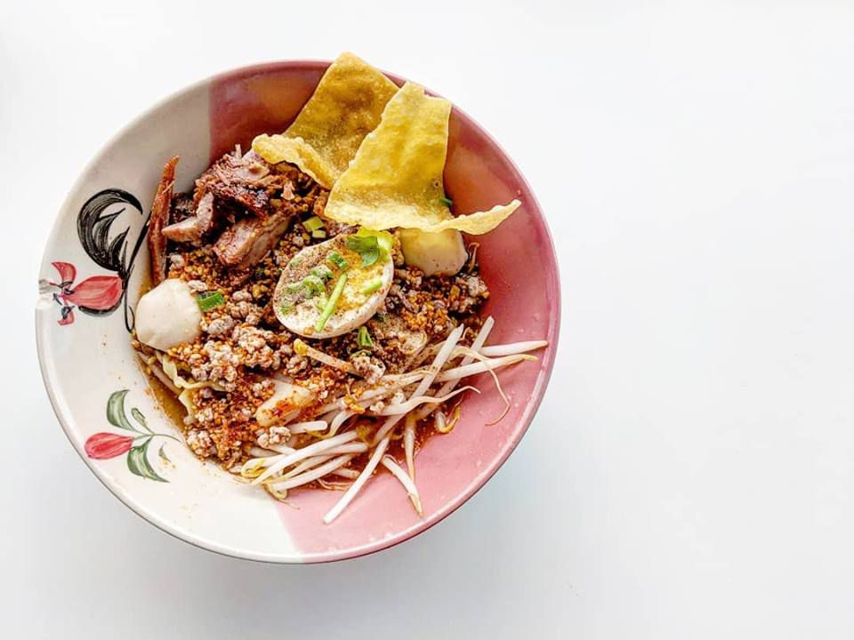 Overhead view of a bowl of a Thai noodle soup with ground pork, bean sprouts, crispy wonton strips, fish balls, and more. The bowl is pink and white with a rooster painted on it, and it sits on a plain white background.