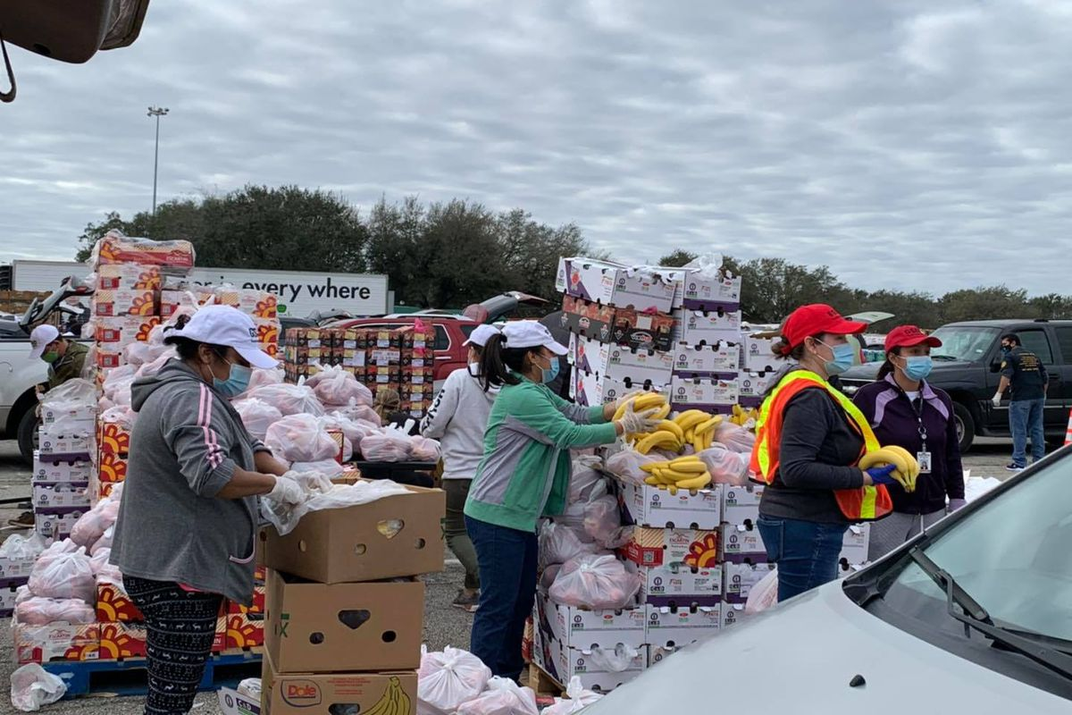 A woman in an orange vest stands in front of a large pile of boxes filled with food donations