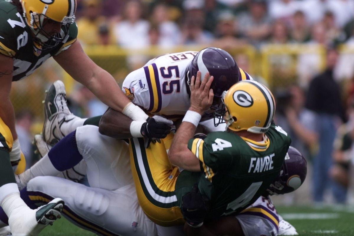 Minnesota Vikings vs green Bay Packers Sept. 26, 1999 — Green Bay Packers Quarterback Brett Favre, 4, is sacked by Minnesota Viking Corey Miller, 55 and Duane Clemmons, 92, during the first quarter at Lambeau Field Sunday.