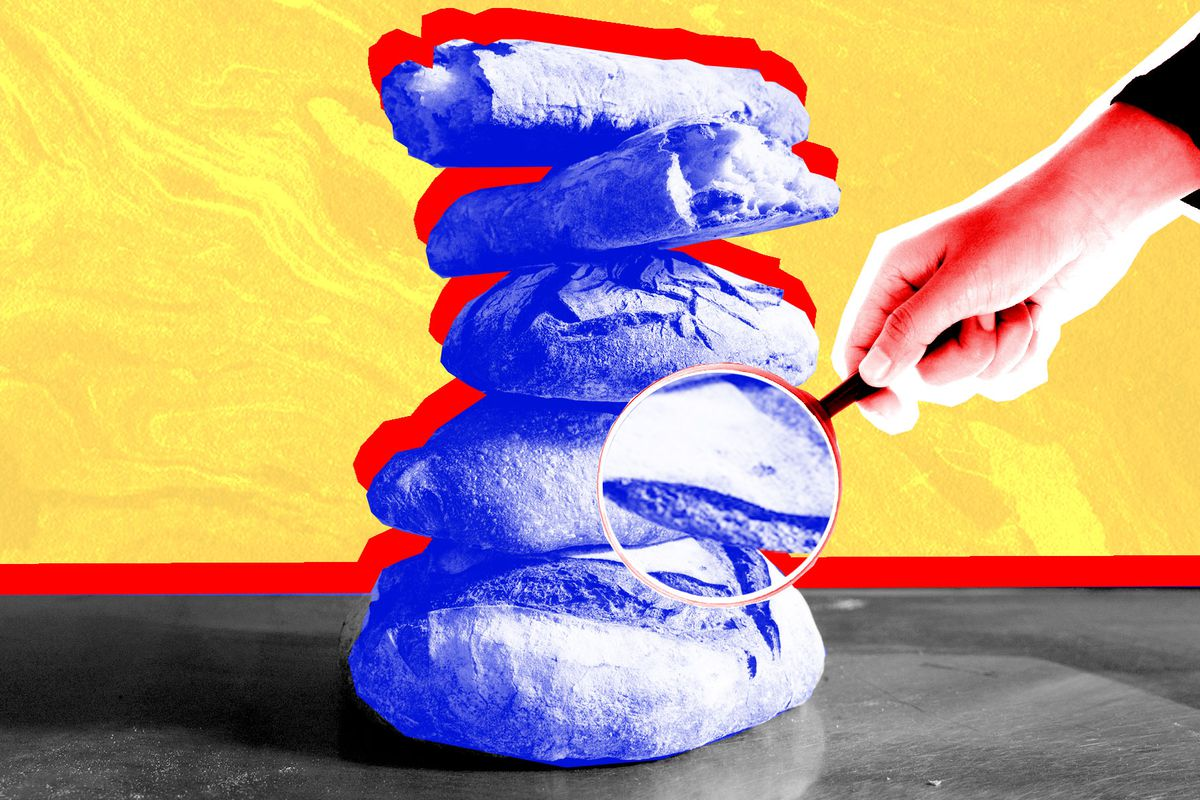 Five loaves of bread stacked atop each other, with a hand holding up a magnifying glass to the stack.