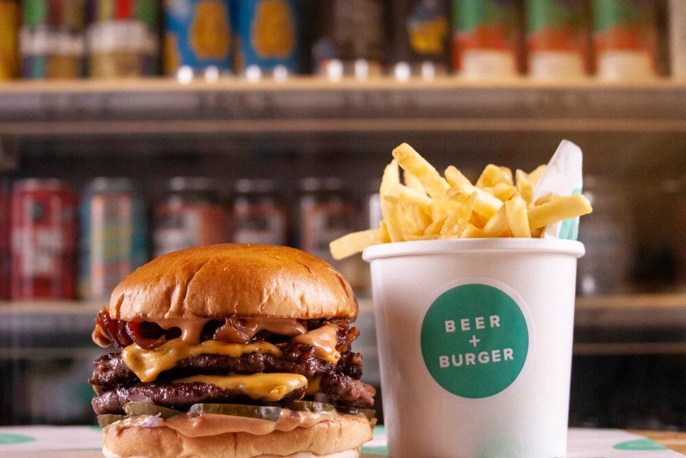 A burger and chips on top of a wooden bar