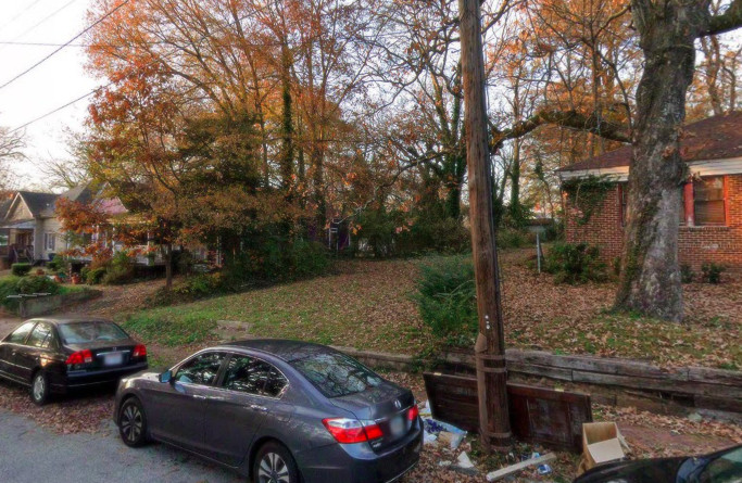 An empty lot surrounded by older homes on a leafy Atlanta street.