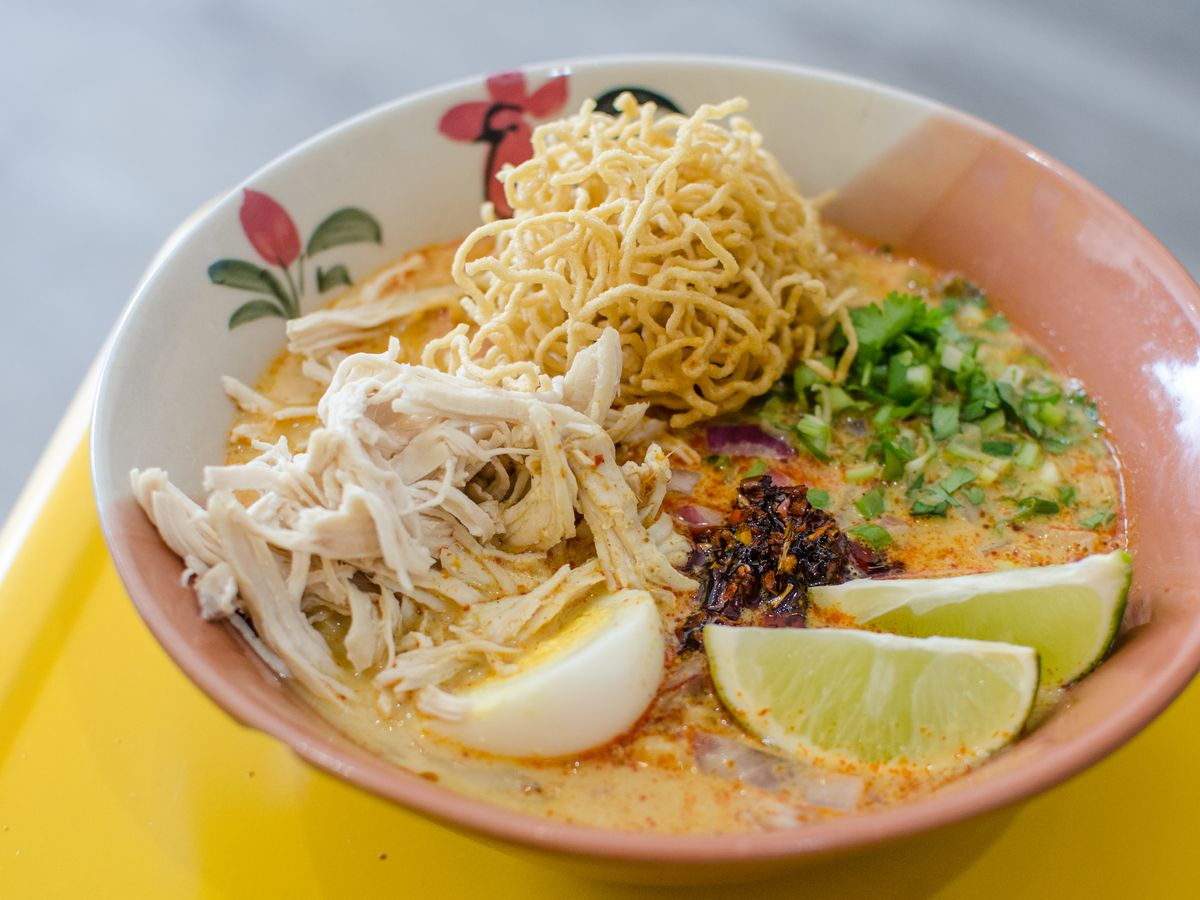 Khao soi —a yellow curry with chicken, egg, lime, crispy noodles, and more —is served in a traditional Thai-style bowl decorated with a rooster. The bowl sits on a yellow surface.