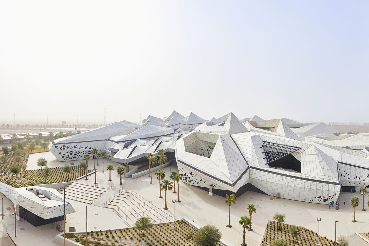 Aerial view of sprawling center made up of hexagonal forms with open courtyards angling outward to the desert landscape.