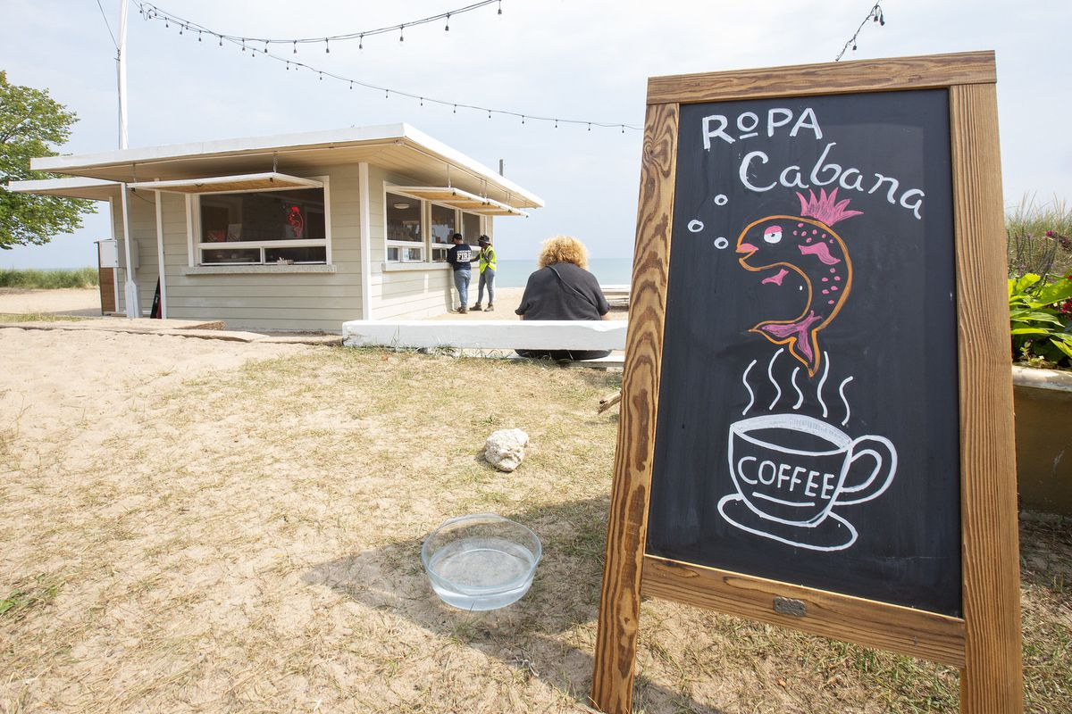 a beach concession stand with a chalkboard sign that says Ropa Cabana