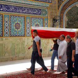 Mourners carry the Iraqi flag-draped coffin of Hamza Jabbar, 37, who was killed from a bomb attack in Karada neighborhood, during his funeral procession at the holy shrine of Imam Ali in Najaf, 100 miles (160 kilometers) south of Baghdad, Iraq, Sunday, July 3, 2016. Dozens of people have been killed and more than 100 wounded in two separate bomb attacks in the Iraqi capital Sunday morning, Iraqi officials said.