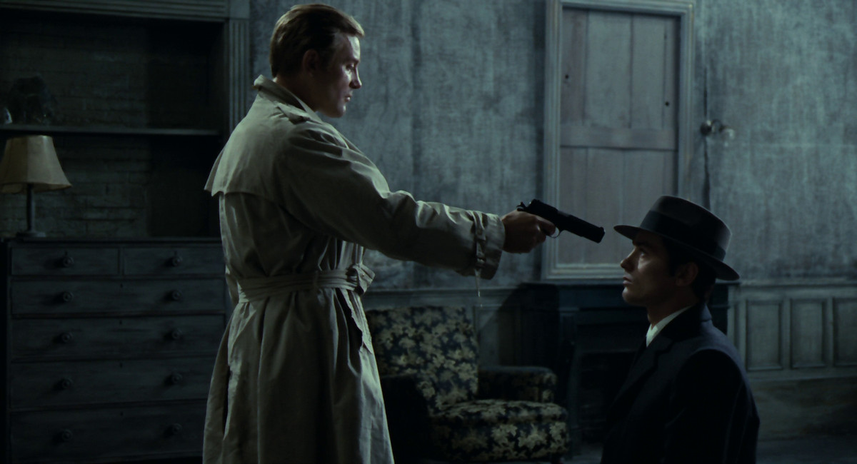 Alain Delon as Jef Costello sits still as a detective points a gun in his face.