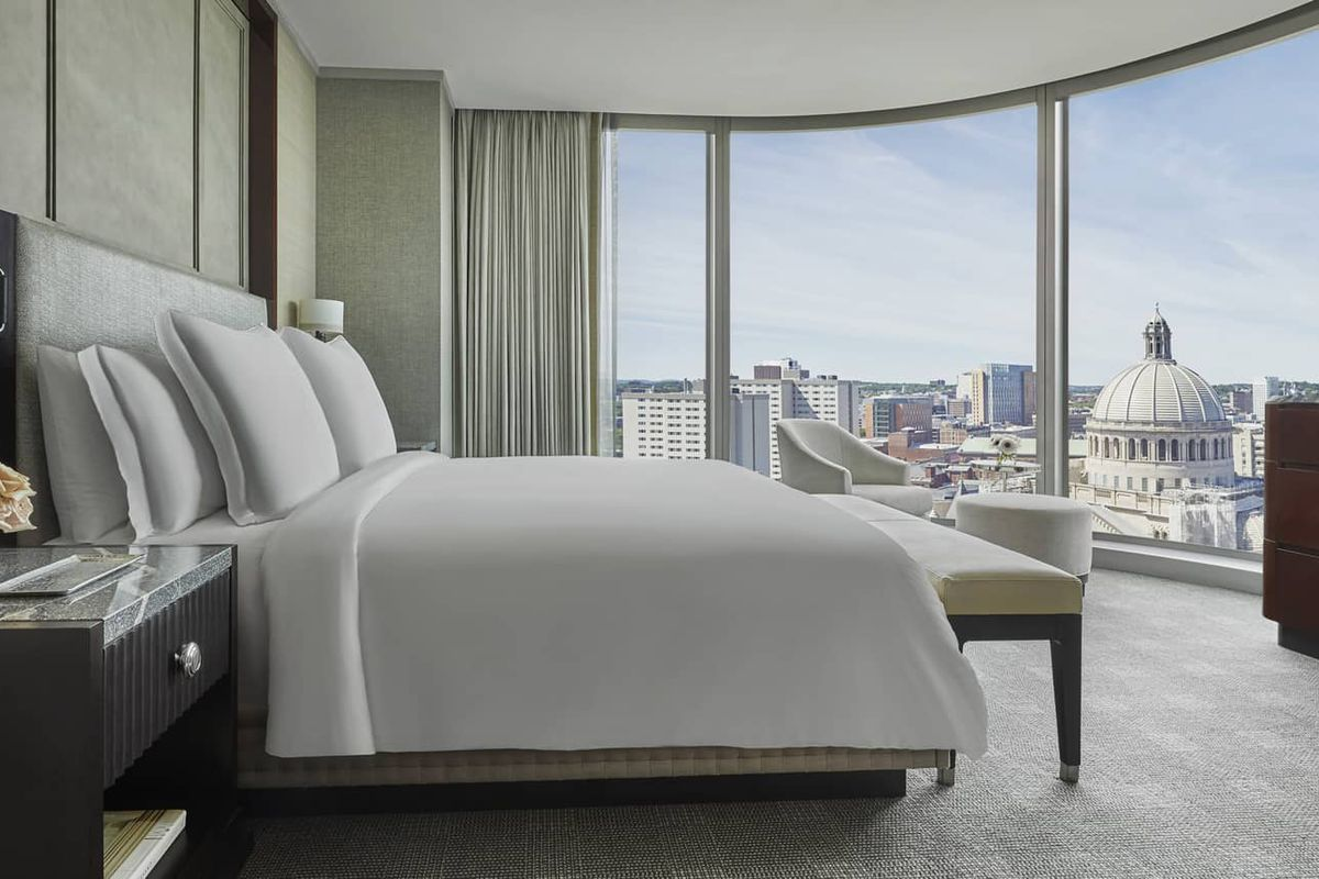 A luxury hotel room with a bed and other furniture inside large windows looking out on a city.