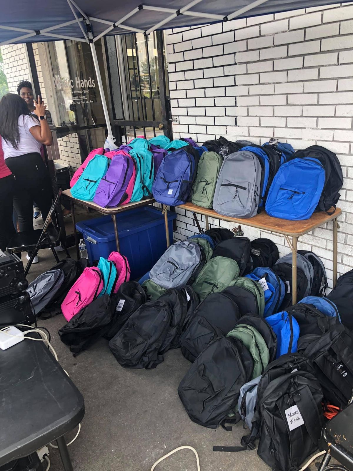 Dozens of new backpacks line a sidewalk waiting to be distributed as part of a back to school supply giveaway.