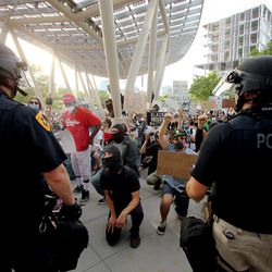 A large group of demonstrators kneel in front of police officers at the Public Safety Building in Salt Lake City on Monday, June 1, 2020.