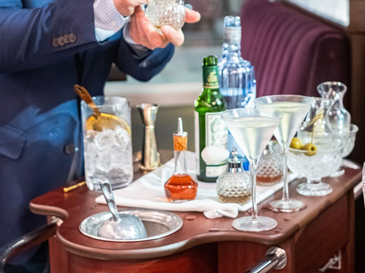 A bartender mixes a martini tableside from an elegant martini cart