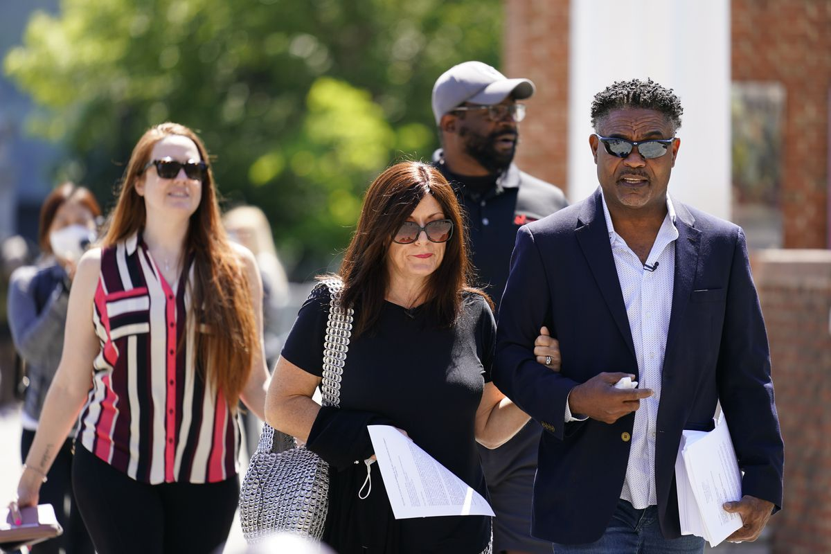 Former NFL players Ken Jenkins, right, and Clarence Vaughn III, center right, along with their wives, Amy Lewis, center, and Brooke Vaughn, left, carry tens of thousands of petitions demanding equal treatment for everyone involved in the settlement of concussion claims against the NFL.
