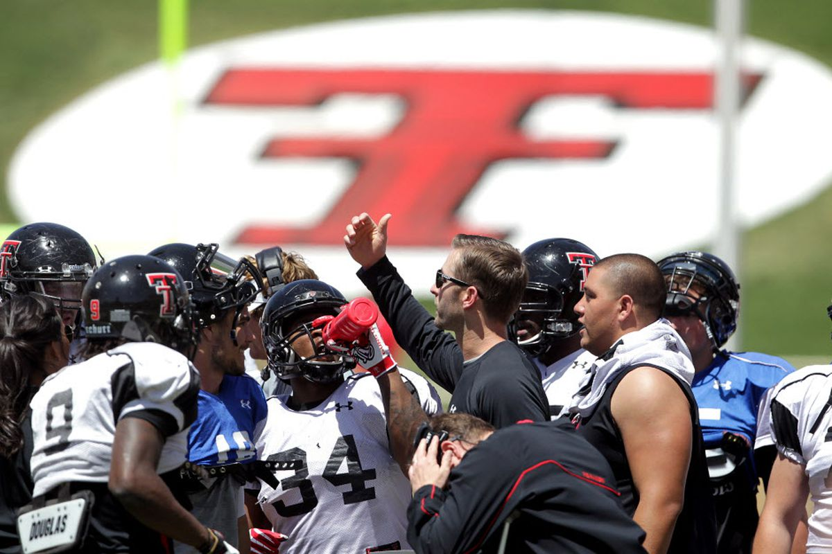 Kliff Kingsbury gathers his offense during the 2014 Spring Game
