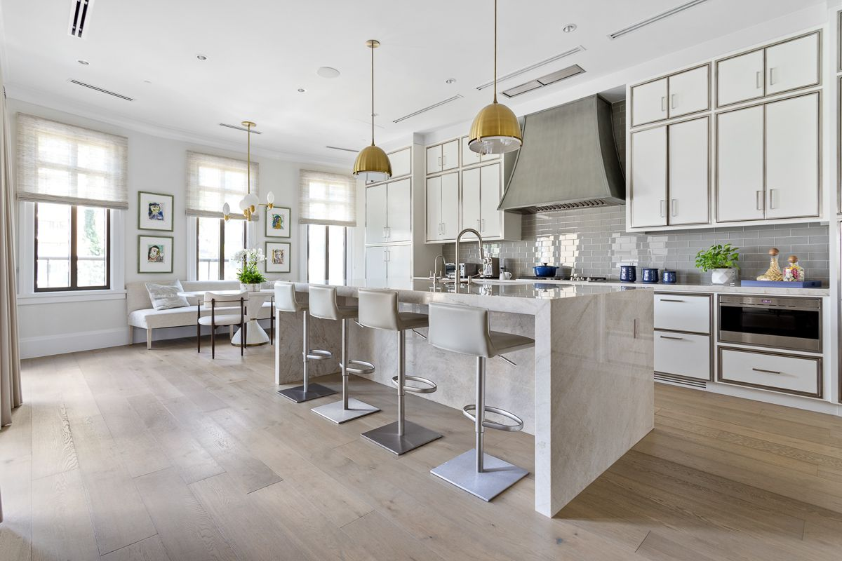 A huge white kitchen with white walls and big windows.