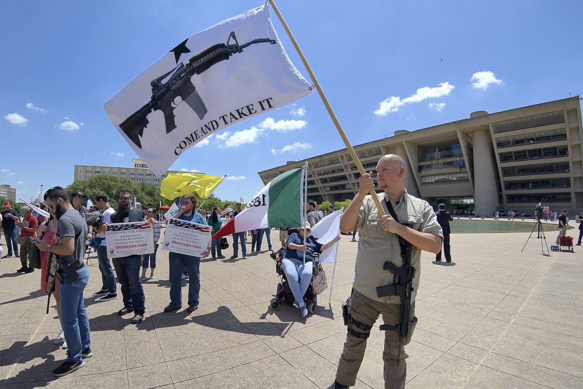 "A man with an AR-15 slung over his shoulder waves a flag depicting an assault rifle along with a message that reads ""Come and take it."""