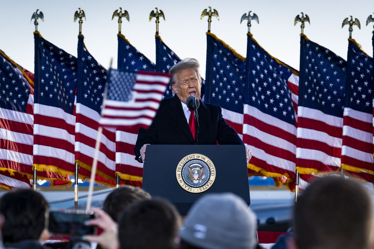 President Trump backed by American flags and speaking to a small crowd on the tarmac at Joint Base Andrews.