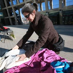Allison Flynn folds clothes while volunteering at the Community Coat Exchange in the Salt Lake City Library Plaza in Salt Lake City on Friday, Nov. 29, 2013.