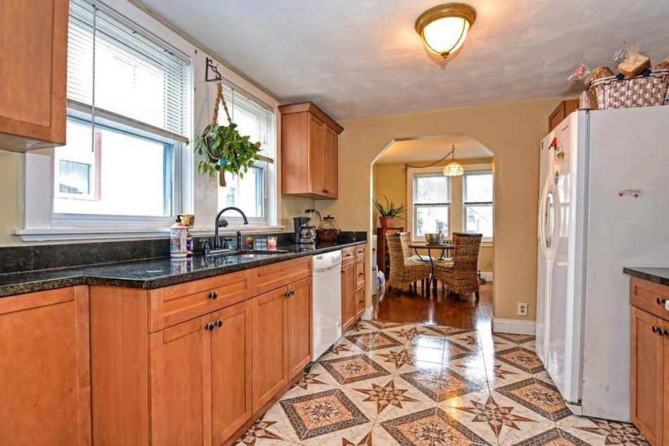 A kitchen with two long counters and a large fridge.