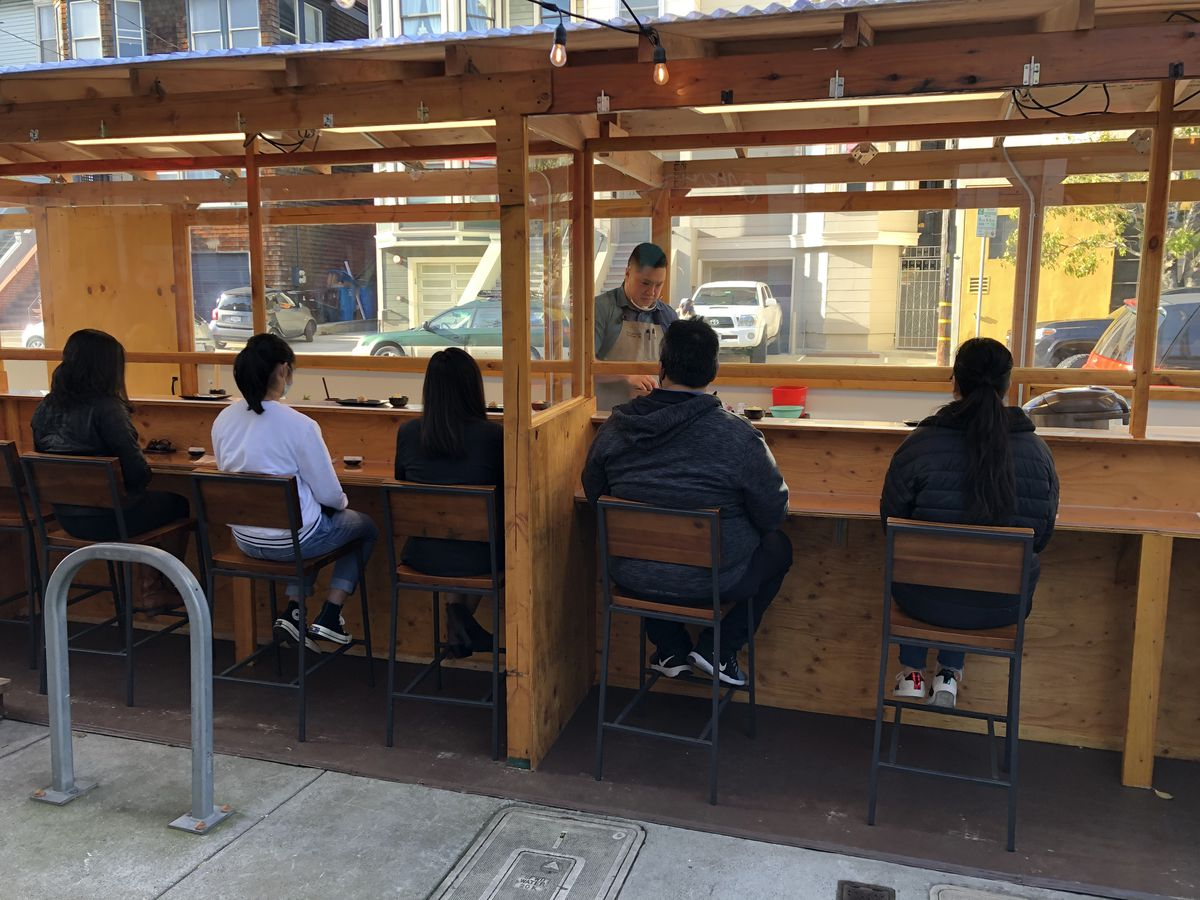 Five customers sit at an outdoor dining structure made from plexiglass and wood. In front of them, a chef prepares pieces of sushi.