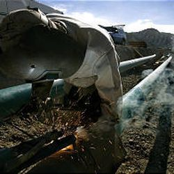 Raymond Davis welds pipe that will connect oil fields to a storage facility belonging to Wolverine Gas and Oil south of Sigurd, Sevier County.