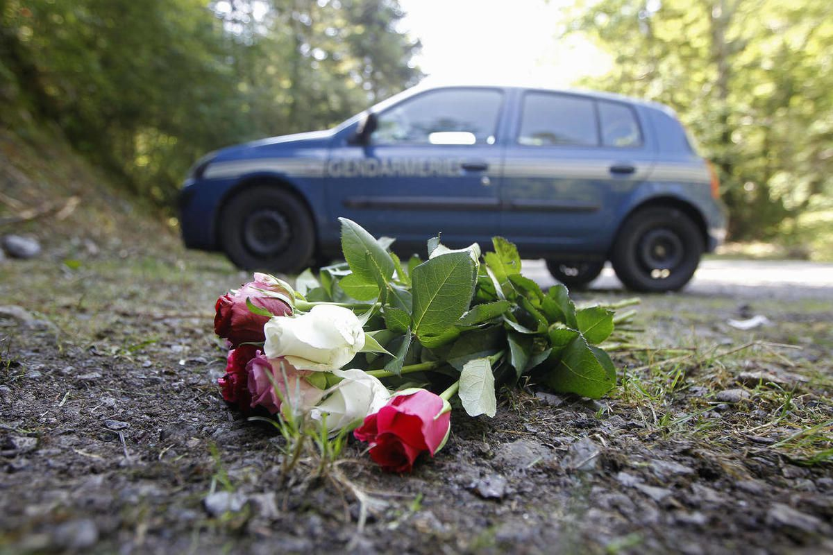 FILE - In this Sept. 8, 2012 file photo flowers are seen at the crime scene where four people have been shot to death in a British-registered car, in a forest in the Alps, near Chevaline, French Alps. The young sisters who survived the mysterious shooting