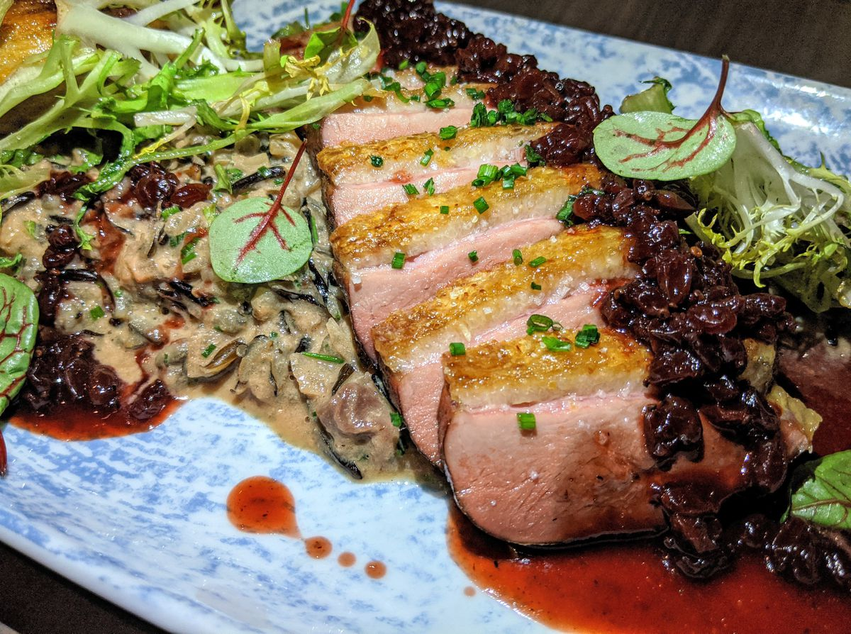 Slices of duck breast on a blue plate with berries, frisee, and a creamy dirty rice