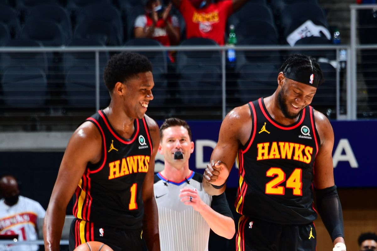 Nathan Knight #1 of the Atlanta Hawks smiles with Bruno Fernando #24 of the Atlanta Hawks during the game against the Houston Rockets on May 16, 2021 at State Farm Arena in Atlanta, Georgia.