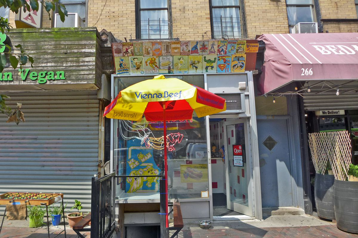 A small storefront with a red and yellow umbrella in front.