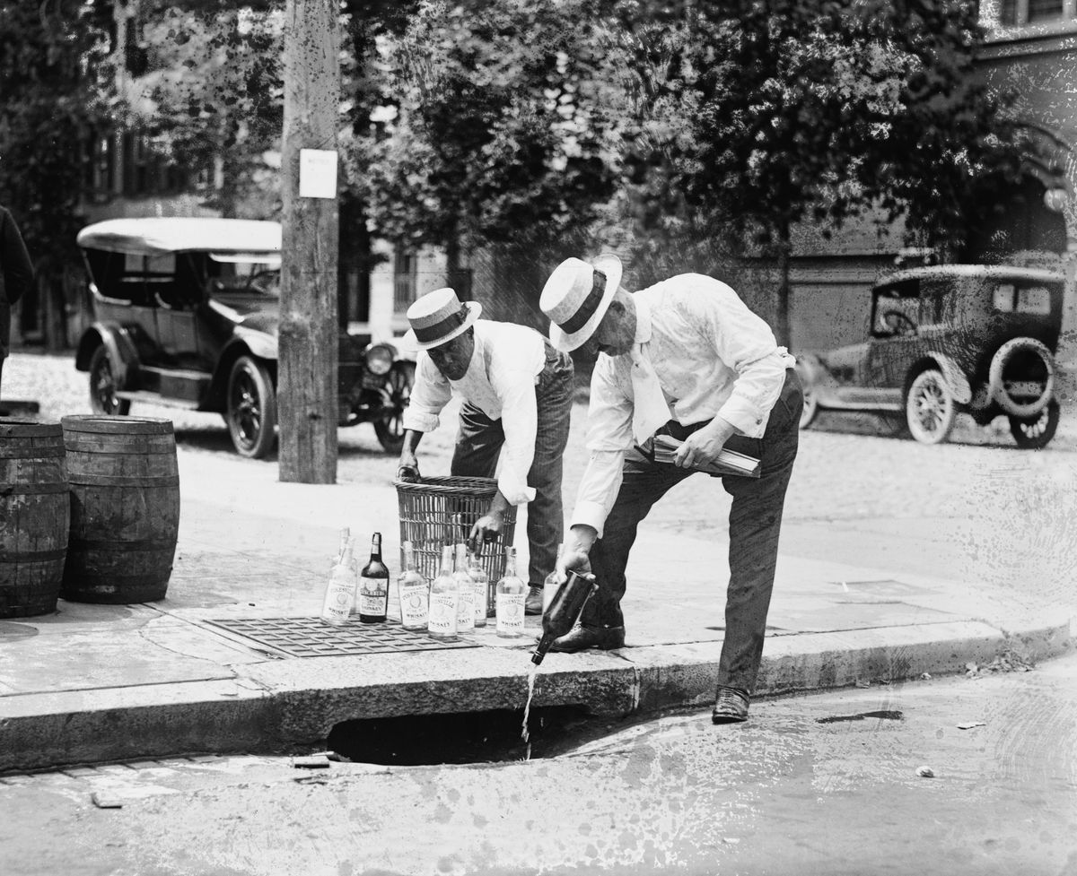 Agents pour liquor into a sewer during Prohibition.