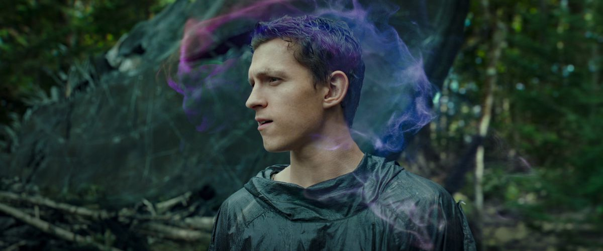 Todd (Tom Holland) looks around a forest while a wispy cloud of purple and pink swirls around his head in Chaos Walking