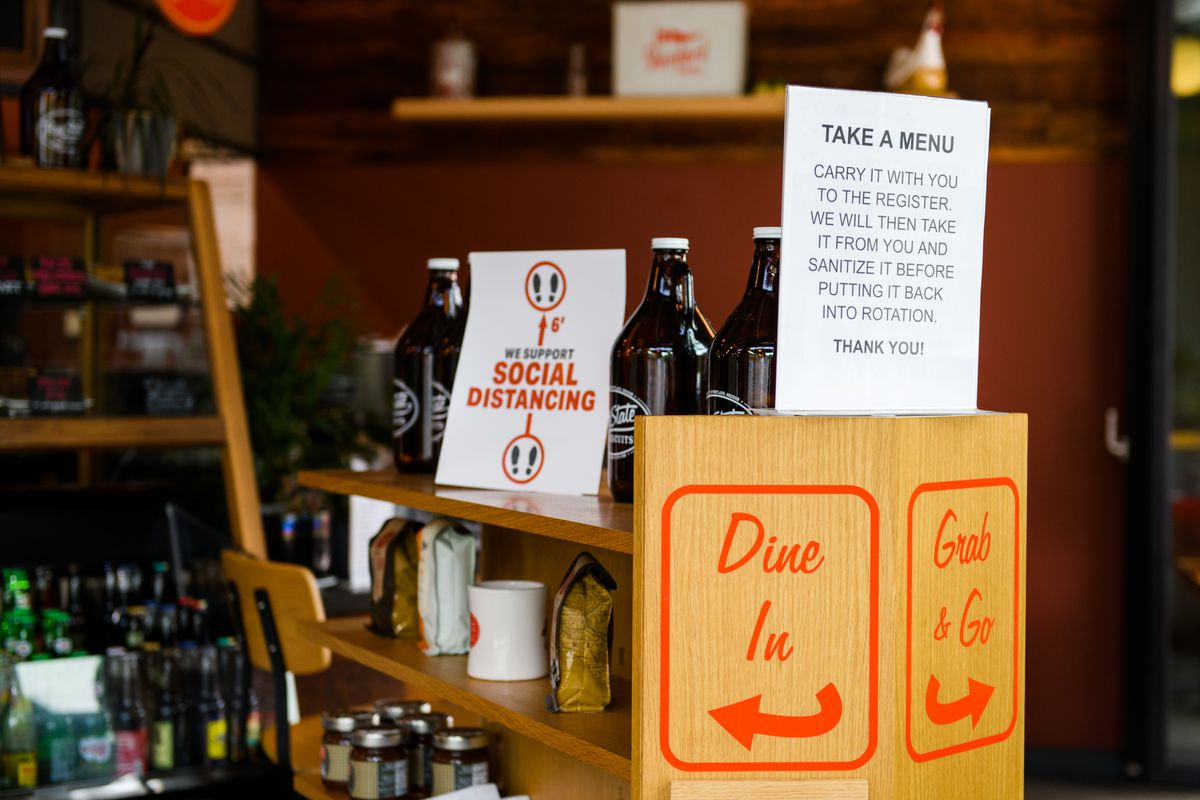 Some growlers sit on a wooden shelf next to a sign, directing customers to either go left for dine-in or right for grab-and-go.
