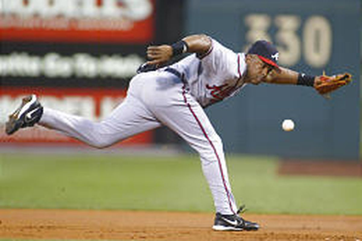 Atlanta's Julio Franco tries but can't quite get to the ball on a triple by Philadelphia's Kenny Lofton.