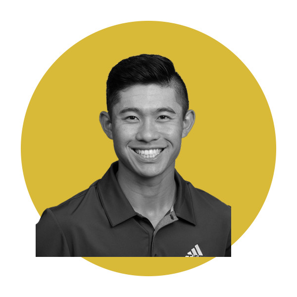 In black and white, golfer Collin Morikawa smiles while wearing a black golf shirt.