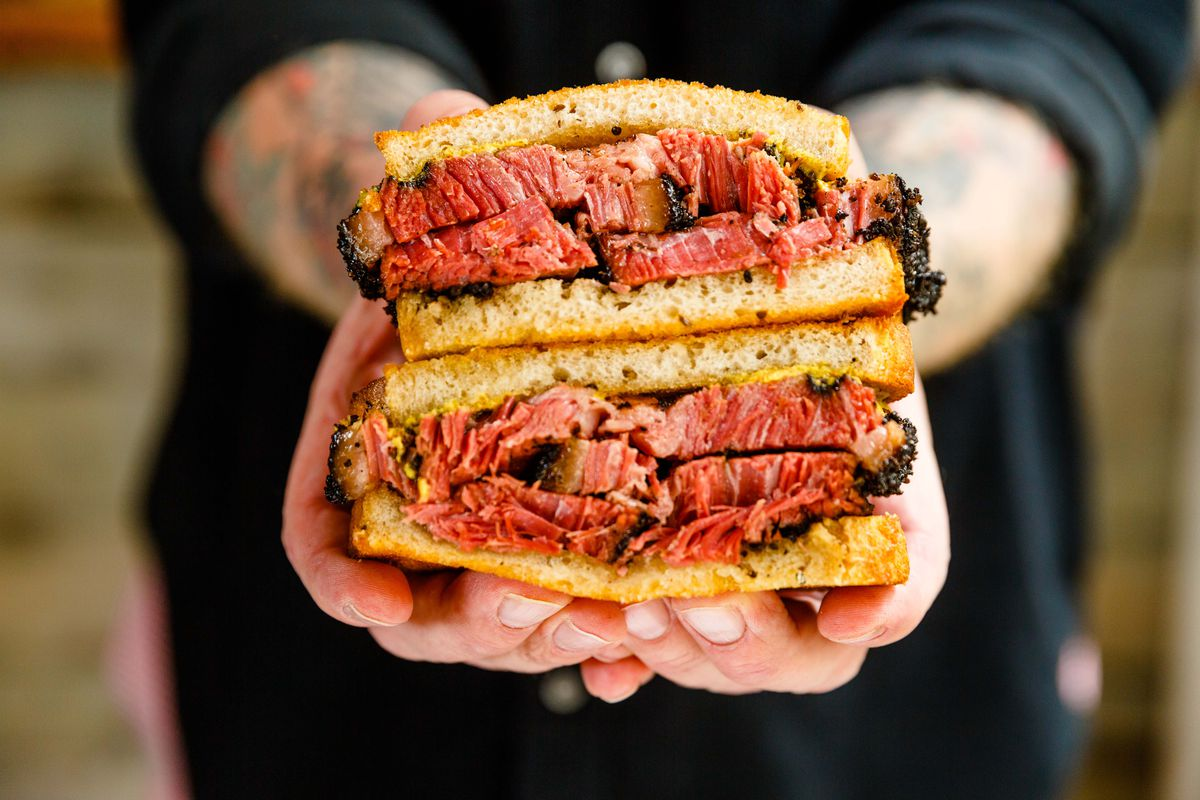 A pastrami sandwich held by two hands