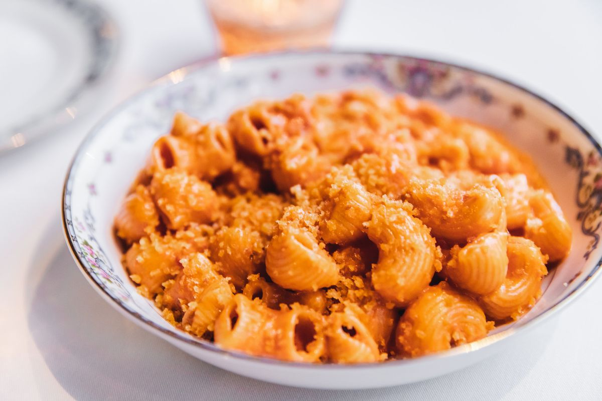 A bowl of short, fat, ridged noodles covered in orange sauce and cheese.