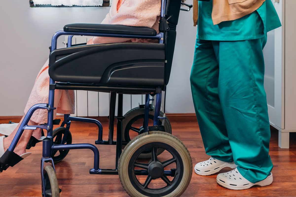 A doctor in surgical scrubs and Crocs pushes a person in a wheelchair.