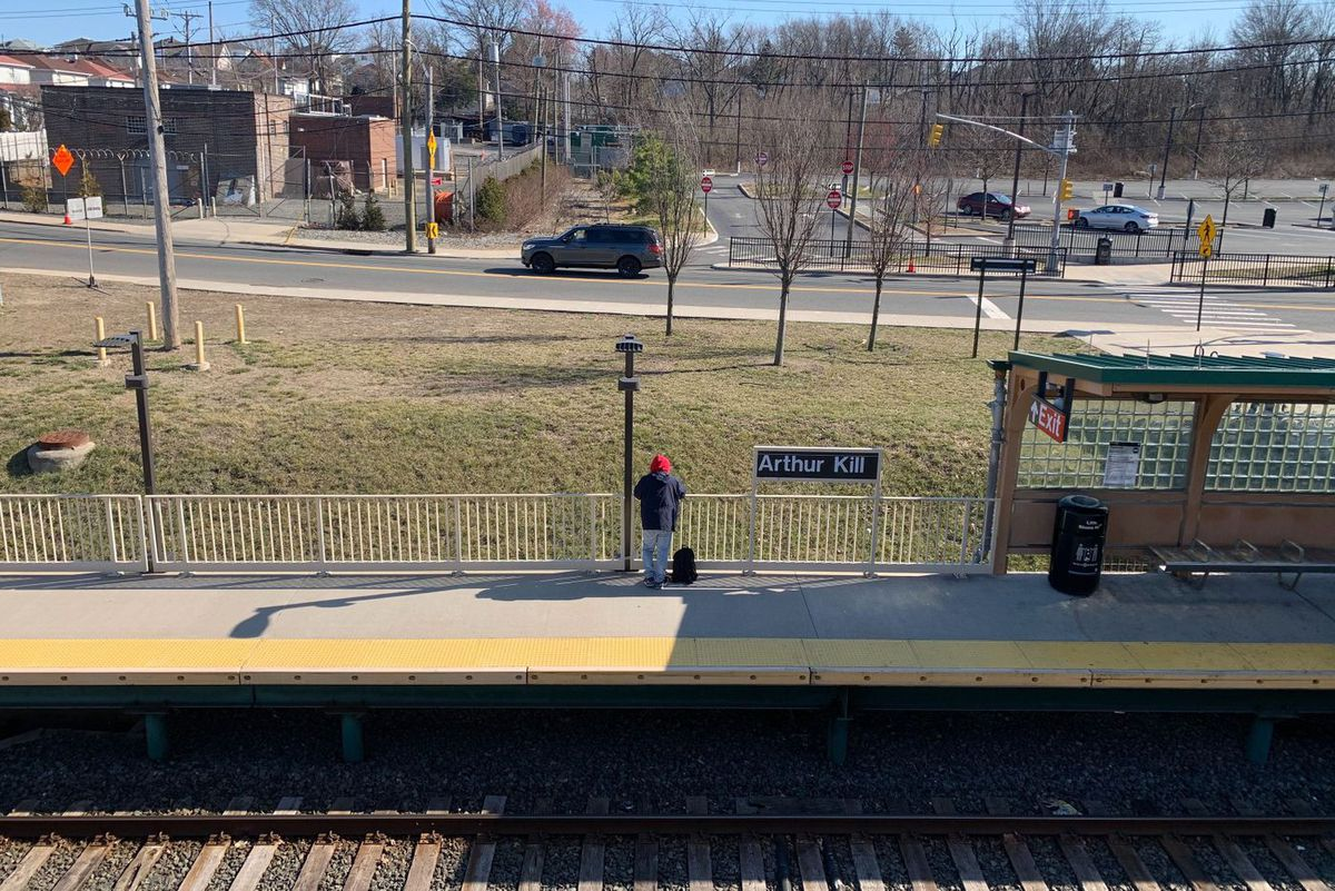 A passenger waits for a St. George bound Staten Island Railway train on Sunday at Arthur Kill.