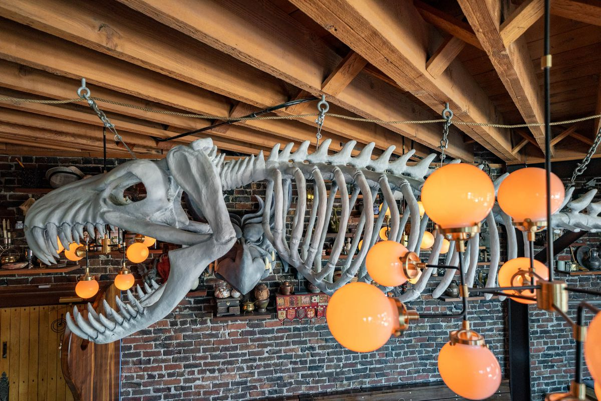 The sculpture inside the Splintered Wand of a giant sea monster skeleton hangs from the wood-beamed ceiling.