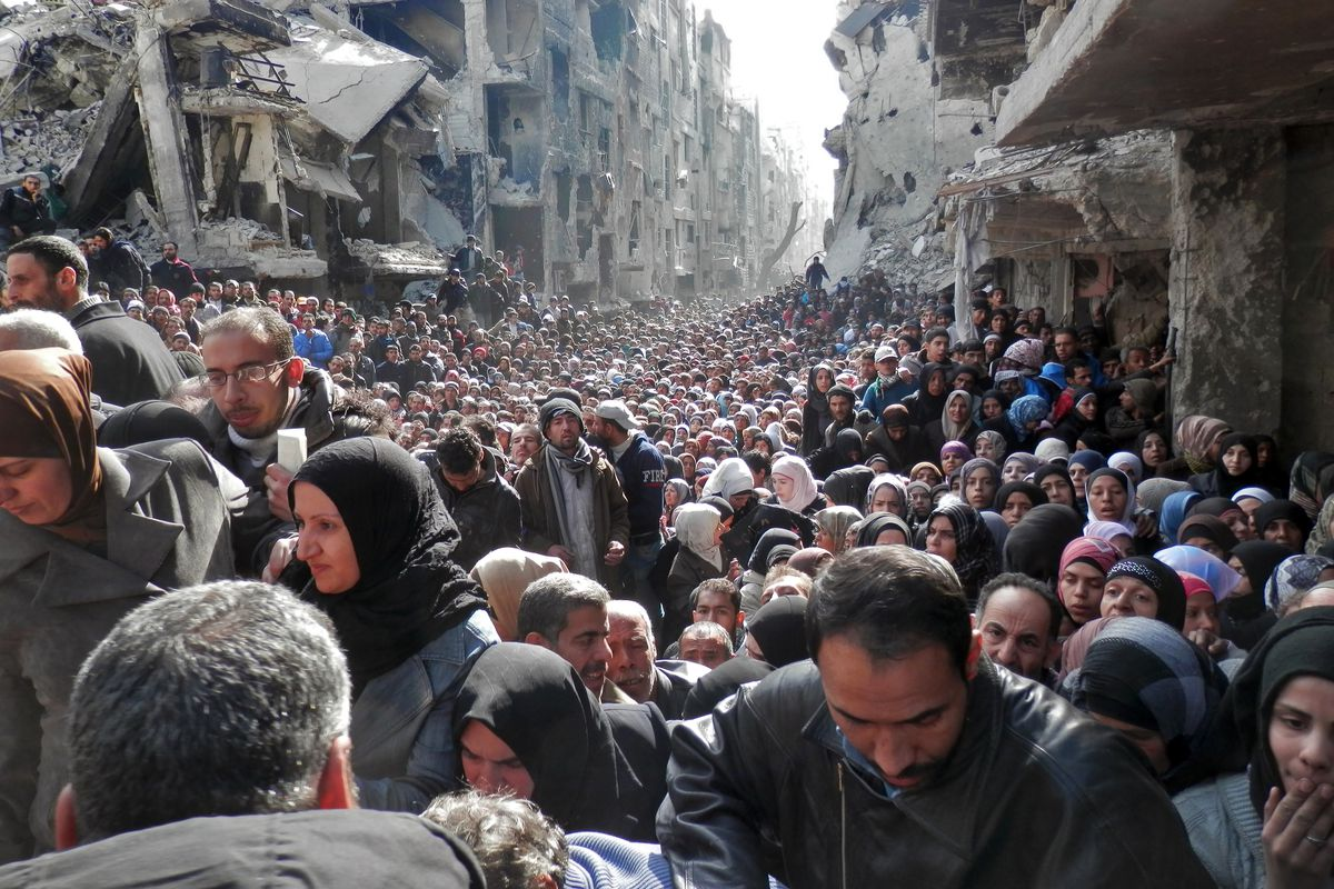 Residents of the Yarmouk refugee camp waiting in line for food aid in January 2014.