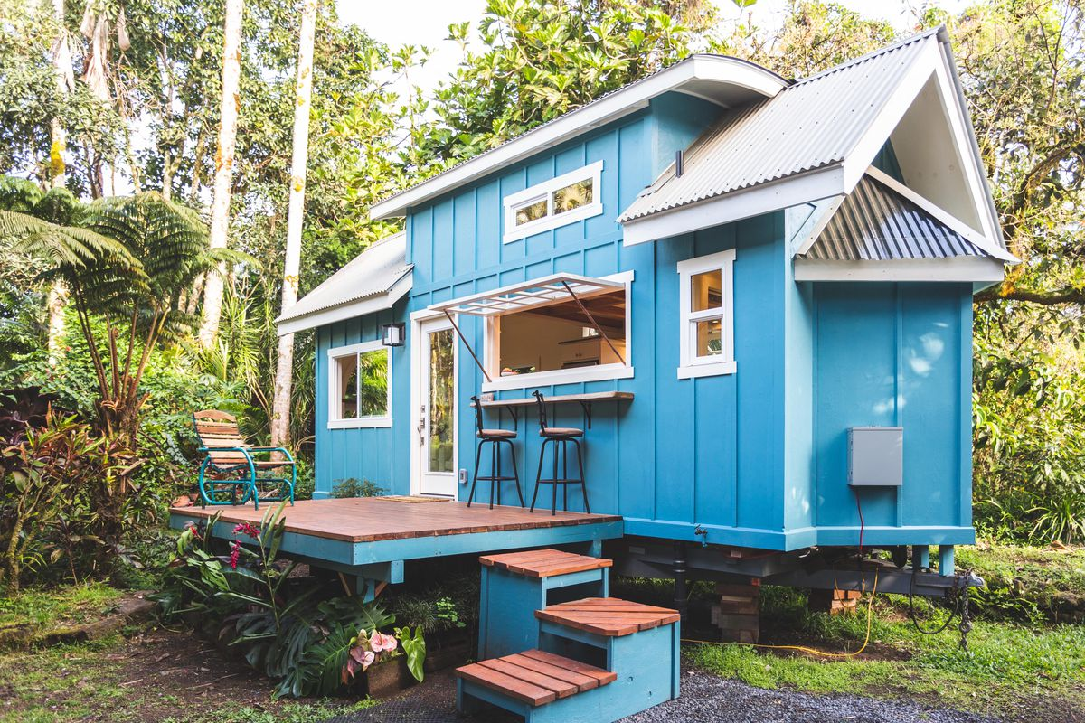 Blue tiny house with a deck and bar seats.