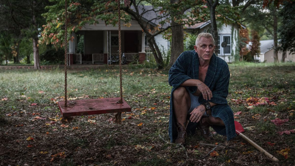Daniel Craig, with bleached hair and a bathrobe, crouches in the yard.