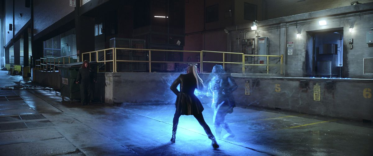 Glowing hero and villain clash in a loading bay outside a building in Thunder Force