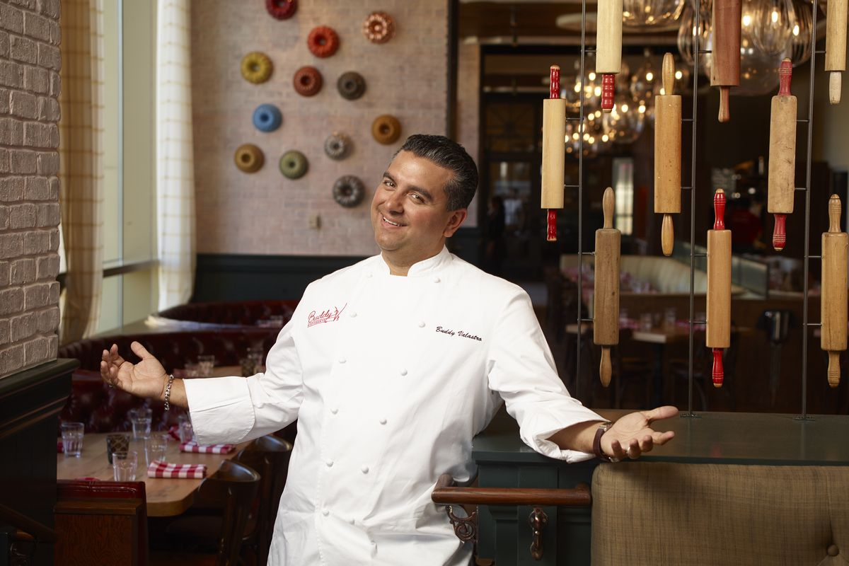 """""""Cake Boss"""" tv star Buddy Valastro stands in his signature pose, arms open to welcome guests to his restaurant."""