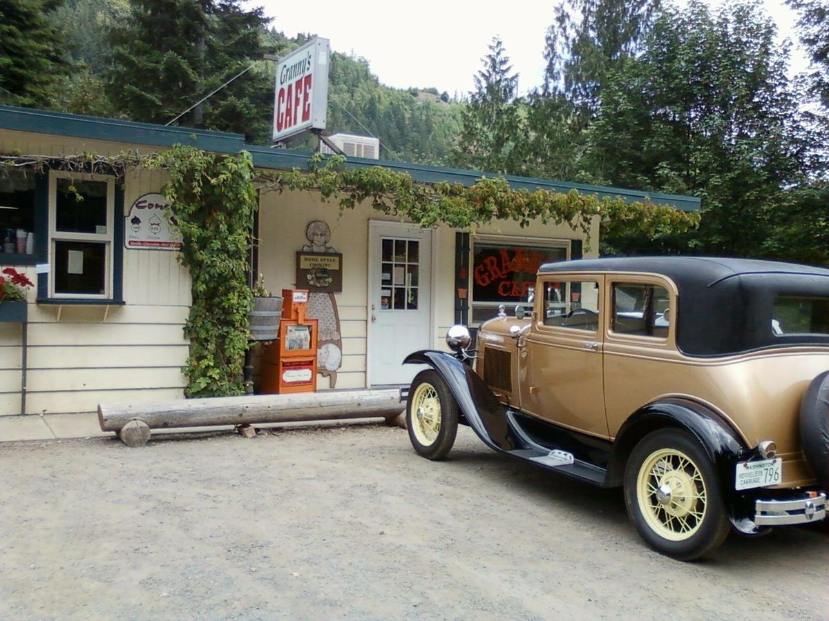 The exterior of Granny's Cafe in Port Angeles, with greenery lining the front porch and a vintage gold car parked outside