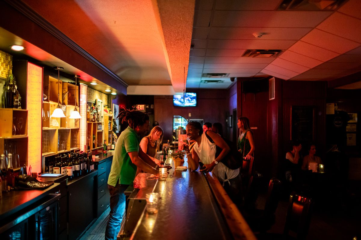 a black bartender with a green shirt and dreadlocks tied back leans over a long dark bar to chat with a black woman with short hair and a white shirt. A glowing red menu display casts red light over the drop ceiling.